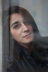 Attractive woman standing behind the glass looking at camera