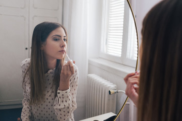 Beautiful Brunette Woman Putting Lip Gloss