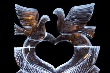 Ice sculpture with a heart and doves. with the flames behind warm.
