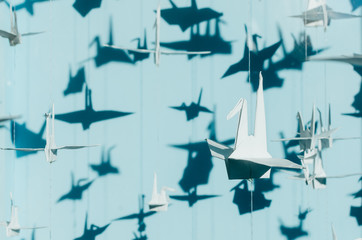 white origami paper cranes hang against blue background