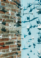 origami crane chains against blue and brick walls