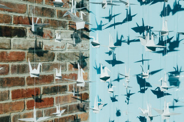 strings of paper cranes with blue and brick background