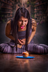 Beautiful and lonely girl suffering from anorexy, suffering pain in his stomach when she looks an apple over a blue plate, in a blurred background