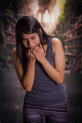 Beautiful and lonely girl suffering of anorexy, putting his fingers in her mouth to induce to vomit, in a blurred background