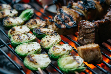 Skewered Brussels Sprouts and meat on a charcoal grill