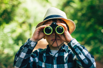 Young boy looking through binoculars in a forest.