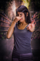 Beautiful and lonely girl suffering from anorexy, holding in her hand a piece of chocolate and covering her nose to do not smell the chocolate, in a blurred background
