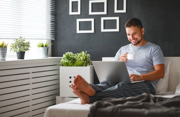 happy young man with laptop and cup of coffee in  the bed