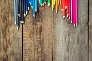 Colored pencils in gradient order located folded on wooden table. School concept. Copy space