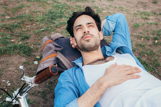 Good-Looking Caucasian Man Lying in Park With Head on Backpack