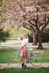 Girl with a pink hair with the bike in the blossoming park