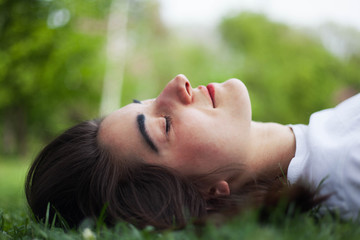 Young woman lying on grass holding her eyes closed