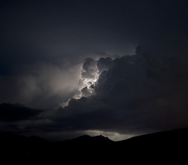 Lightning illuminates clouds in a stormy night sky