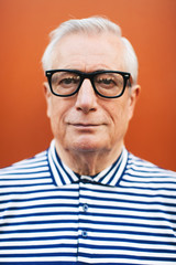 Portrait of an elderly man wearing rimmed glasses standing in front an orange wall.