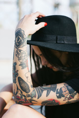Side view of a young alternative woman with tattooed arm sitting on the street.