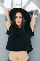 Portrait of a young alternative woman with tattoos standing in the city.