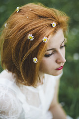 Ginger woman with chamomile in her hair