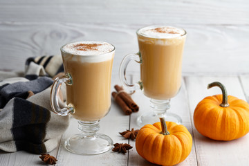 Fall pumpkin spice latte with whipped cream and cinnamon, ornamental pumpkins and warm woolen scarf on white wooden background