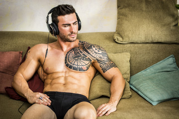 Handsome shirtless muscular bodybuilder man listening to music with headphones while sitting on couch