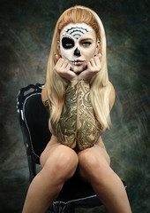 Front portrait of a sitting semi nude female with skull makeup and tattoos . 3d rendering