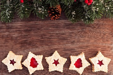 Christmas baking double border on a wooden background with branches and jam cookies