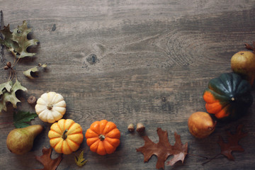 Thanksgiving season still life with colorful small pumpkins, acorn squash, fruit and fall leaves over rustic wooden background