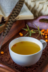 Vitaminic tea with sea-buckthorn on the wooden table