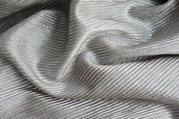 Embossed shiny fabric, pleated. Silver material textile.