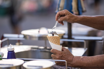 cropped image of old man hands holding waffle cone of ice cream