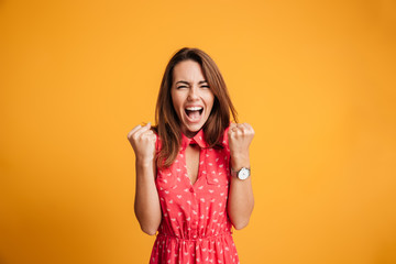 Close-up of emotional brunette woman keeping hands in fists, screaming while celebrating win