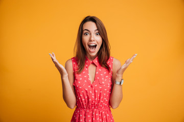 Close-up portrait of young pretty surprised woman with opened mouth standing with open palms