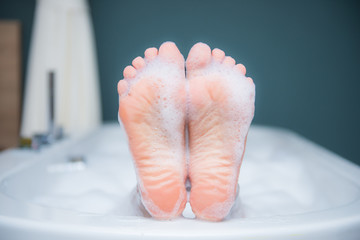 Closeup of woman's foot on the edge of a bath with foam