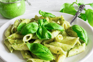 penne pasta with basil pesto and herbs in a plate with fork