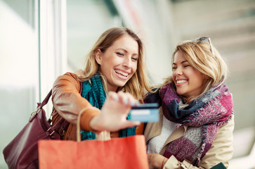 Happy woman with shopping bags holding credit card