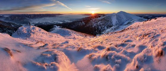Panoramic view of beautiful winter wonderland mountain scenery in evening light at sunset
