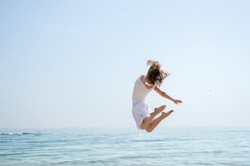 Happy beautiful young girl jumping