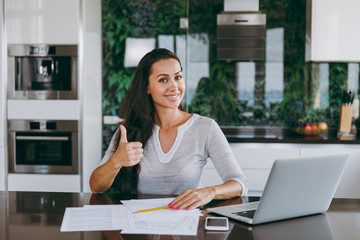 Attractive young modern business woman shows thumbs gesture cool and working with documents and laptop in the kitchen at home