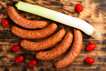 Five deliciously smoked handmade Swedish Isterband sausages with natural casing. Here on burnt wooden cutting board with red tomatoes and leek.