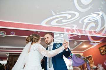Beautiful wedding couple performing their first dance in the restaurant with different lights and bubbles and guests on the background.
