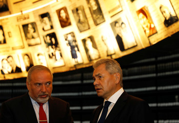 Russian Defence Minister Shoigu stands next to his Israeli counterpart Lieberman as as they look at pictures of Jews killed in the Holocaust during a visit to the Hall of Names at Yad Vashem's Holocaust History Museum in Jerusalem