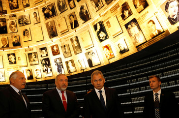 Russian Defence Minister Sergey Shoygu stands next to his Israeli counterpart Avigdor Lieberman as they look at pictures of Jews killed in the Holocaust during a visit to the Hall of Names at Yad Vashem's Holocaust History Museum in Jerusalem