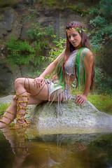 Junge Frau sitzt verführerisch am Wasser