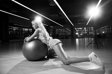 Seductive blonde woman, dressed in fitness clothing, standing half-turned on her knees on wooden floor and leaning on large gray exercise ball. Attractive fitness model posing in sexy position