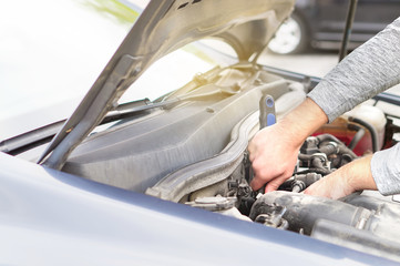 Man fixing engine under the hood. Car repair, maintenance and vehicle inspection concept.