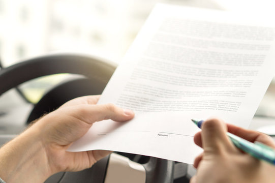 Signing lease or buying new or used car. Man about to write autograph to legal document. Motor vehicle insurance agreement. Rental contract paper.