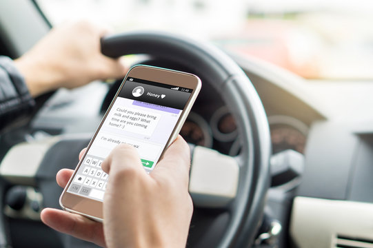 Texting while driving car. Irresponsible man sending sms and using smartphone. Writing and typing message with cellphone in vehicle. Holding steering wheel with other hand.