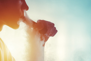 Man smoke an electronic cigarette mechanical mod on the light background
