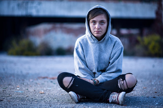 Woman with Sweatshirt and Torn Trousers Sitting on the Street