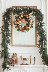 Decorations on the Christmas fireplace in the form of candlesticks, Christmas wreath and photo frame, vintage doll, small toy horse