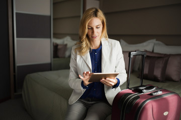 Portrait of attractive businesswoman using tablet on bed